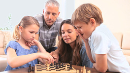 Happy family playing chess Footage