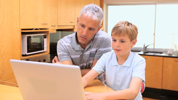 Smiling boy using a laptop with his father Footage