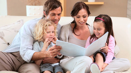 Smiling family reading a book Footage