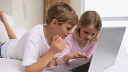 Cheerful siblings using a laptop Footage