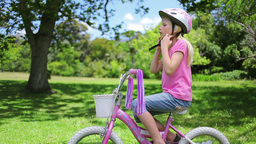 Girl puts on a cycling helmet and holds the handle Footage