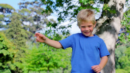 Boy jumping in a park with his arms raised Footage
