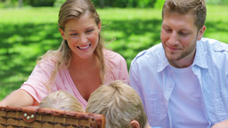 Two children reach into a picnic basket while sitt Footage