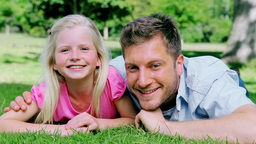Man looks at his daughter with a confused look before smiling as they lie on the grass Live Action