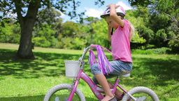 A girl picks her helmet out of a bike basket and p Footage