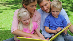 A family turning the page of a book and then conti Footage