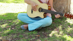 Camera rises to show a girl playing guitar in the  Footage