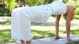 A woman holding a yoga position in the park Footage