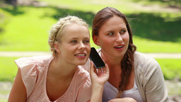 Two shocked women listen to someone on the phone Footage