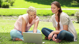 Two women sit on the grass as they use a laptop to Footage