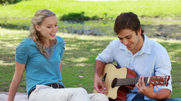 A man plays guitar and sings to a woman as they si Footage