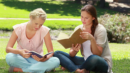 Two women read books in the park as one shows her  Footage