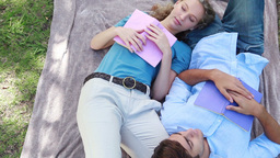 A couple sleep beside each other with books in the Footage