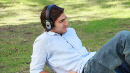 A man lies on the ground listening to his headphon Footage