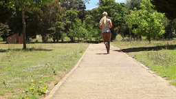 A woman jogs past the camera and down a footpath Footage