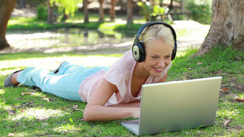 A woman lies in the park with headphones on while  Footage