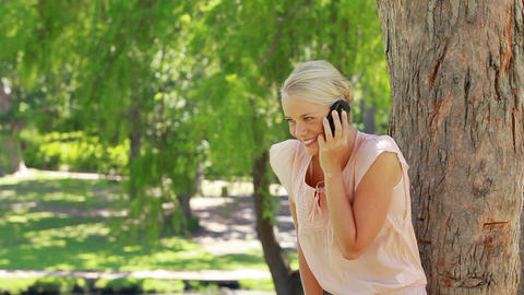 A woman standing by a tree talking on her phone as Footage