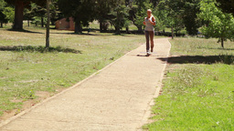 A woman jogs up a footpath past the camera Footage