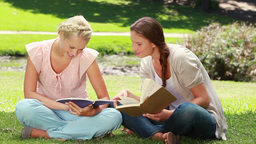 Two ladies reading in the park as they then look a Footage