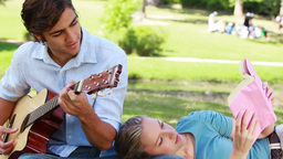 Man practises guitar as the woman rests on his leg Footage