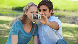 A couple pose for a picture together as they check Footage