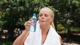A woman takes a drink of water and then wipes her  Footage