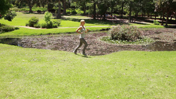 A woman jogs past a pond while the camera pans acr Footage