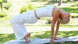A woman performs a yoga position as the camera cha Footage