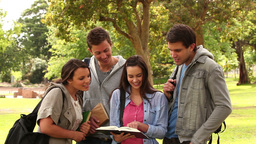 Four friends laughing while pointing at a book as  Footage