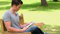 Man reading a newspaper while sitting on a wooden  Footage