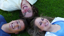 Three friends lying head to head before opening their eyes and smiling Footage