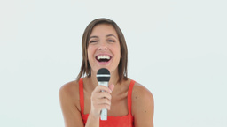 Girl singing into a microphone while smiling Footage