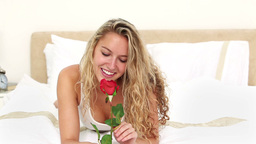 Blonde haired woman smelling a rose Live Action