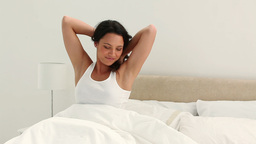 Brunette haired woman wakes up and stretches Footage