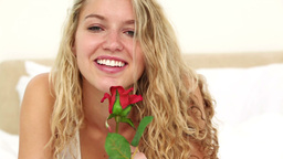 Blonde haired woman smelling a red rose Live Action