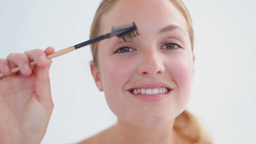 Smiling blonde woman brushing her eyebrows Footage