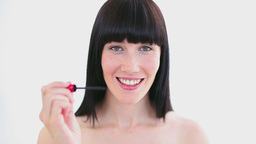 Happy woman applying mascara on her eyelashes Footage