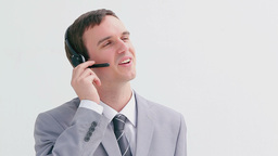 Smiling call centre agent talking into his headset Live Action