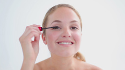 Smiling blonde applying mascara on her eyelashes Footage