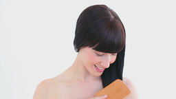 Smiling brunette brushing her hair Footage