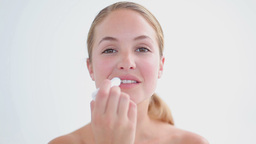Smiling blonde woman using a lip balm Footage