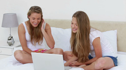 Friends laughing while watching a video on a lapto Footage