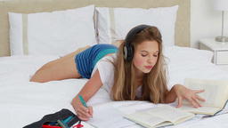 Young woman studying while listening to music Footage