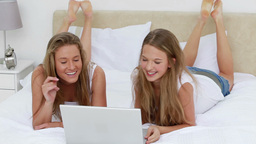 Happy women lying while looking at a laptop Footage