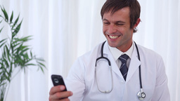 Happy doctor sending a text message Live Action