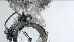 Alarm clock in super slow motion falling in the water Footage