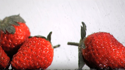 Strawberries in super slow motion receiving drops Footage