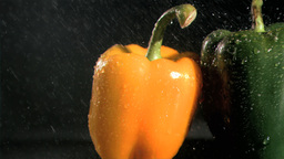 Raindrops in super slow motion falling on peppers Footage