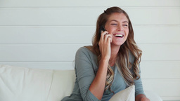 Woman laughing as she talks on a phone Footage