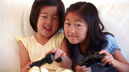 Two girls playing a games console together Live Action